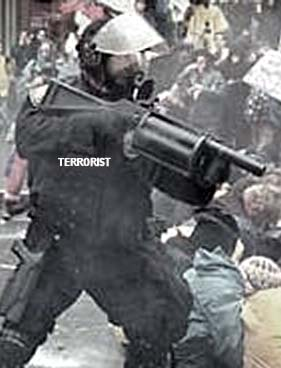 "policeperson opens fire on crowd, uniform bears the legend ""Terrorist""."